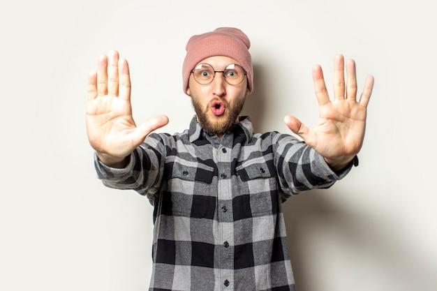 Jeune homme avec une barbe dans un chapeau, une chemise à carreaux étendit ses mains devant lui avec ses paumes au spectateur sur un blanc isolé. arrêtez le geste, assez