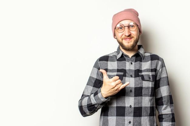 Jeune homme avec une barbe dans un chapeau, une chemise à carreaux fait un geste de shaka sur un blanc isolé. geste de salutation