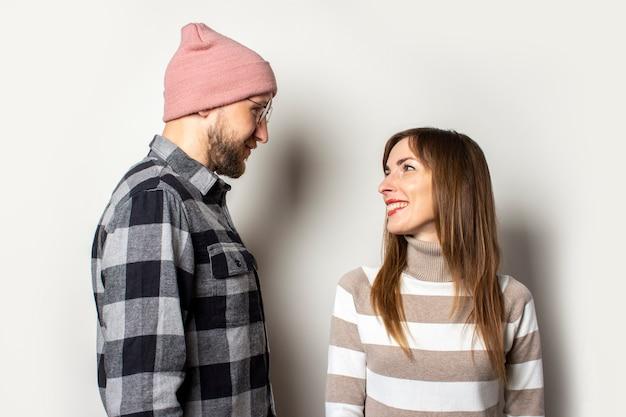 Jeune homme avec une barbe dans un chapeau et une chemise à carreaux et une fille dans un pull se regardent sur une lumière isolée