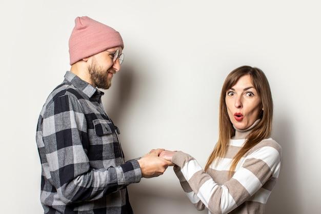 Jeune homme avec une barbe dans un chapeau et une chemise à carreaux et une fille dans un pull se tiennent la main, une fille avec un visage surpris sur un isolé