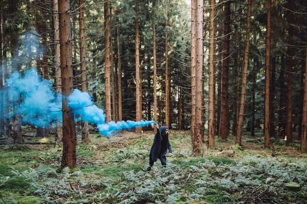 Jeune homme à la barbe dans la forêt tient la fumée bleue