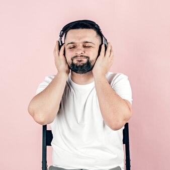 Un jeune homme avec une barbe dans de gros écouteurs noirs. passe-temps et loisirs.
