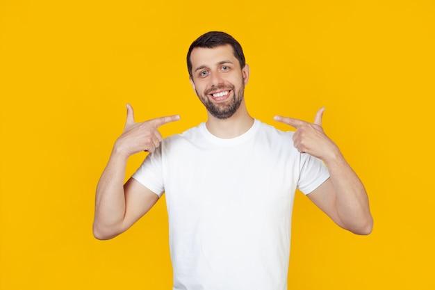 Jeune homme avec une barbe dans un t-shirt blanc visage heureux souriant avec confiance montrant et pointant avec les dents et la bouche des doigts.