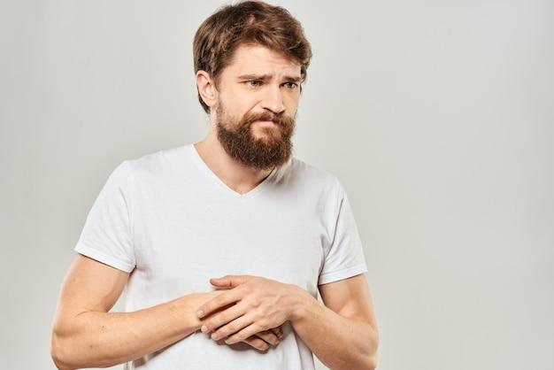 Un jeune homme avec une barbe dans un t-shirt montre différentes émotions, plaisir, tristesse, colère en studio sur le fond