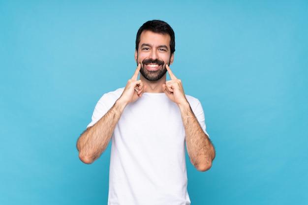 Jeune homme à la barbe sur fond bleu isolé souriant avec une expression heureuse et agréable