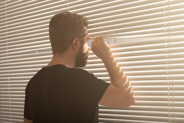 Jeune homme à la barbe furtivement à travers les stores