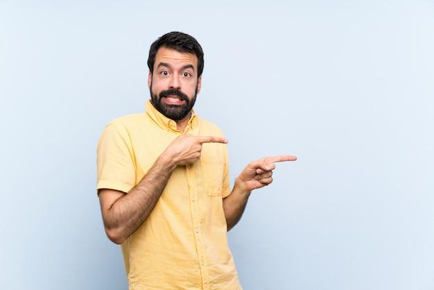 Jeune homme à la barbe isolé bleu effrayé et pointant sur le côté