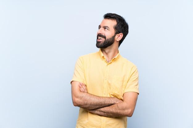 Jeune homme à la barbe isolé bleu heureux et souriant