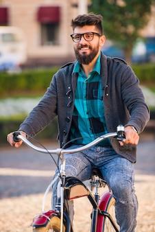 Un jeune homme avec une barbe, marche la ville en vélo