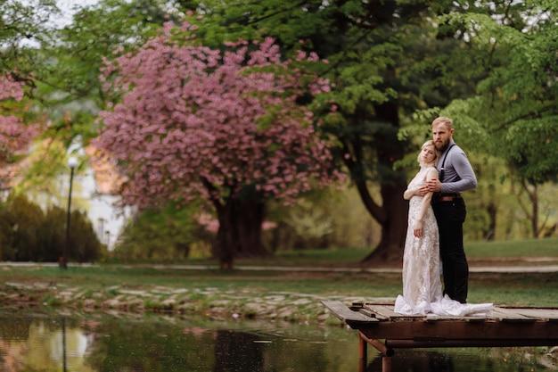 Jeune homme avec barbe et mariée en robe longue de luxe étreignant près du lac dans le parc avec des fleurs de cerisier ou de sakura en fleurs. jour de printemps de mariage
