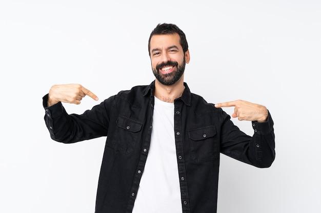 Jeune homme à la barbe sur un mur blanc isolé fier et satisfait