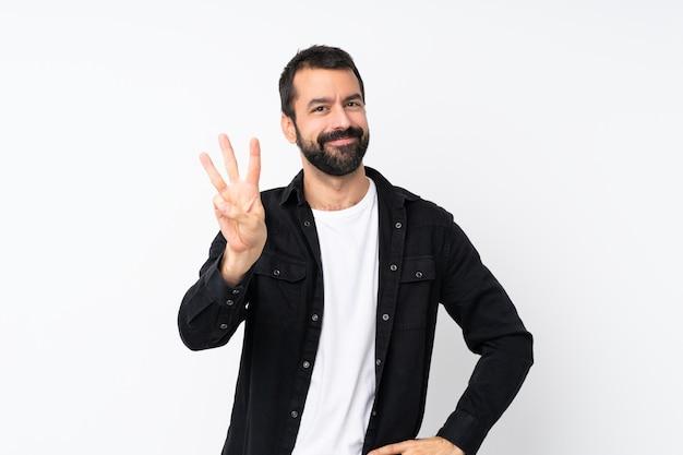 Jeune homme à la barbe sur mur blanc isolé heureux et comptant trois avec les doigts