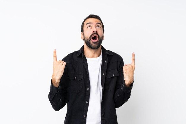 Jeune homme à la barbe sur mur blanc isolé surpris et pointant vers le haut