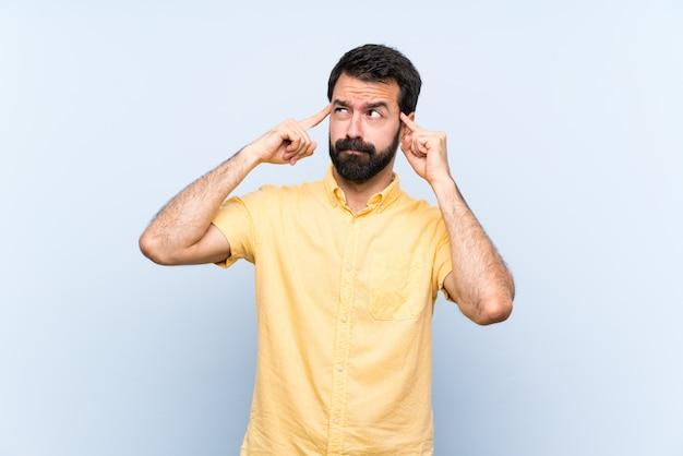 Jeune homme à la barbe sur mur bleu isolé, avoir des doutes et penser