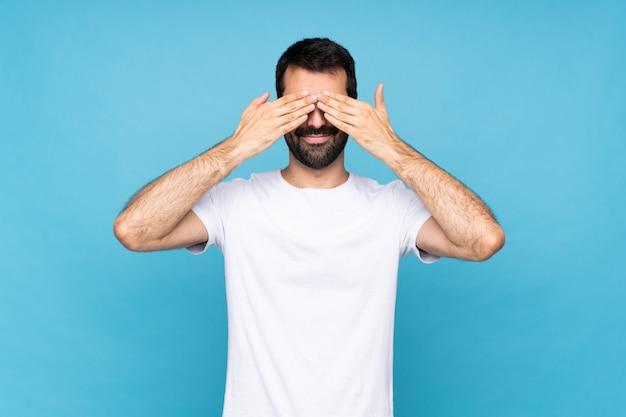 Jeune homme à la barbe sur mur bleu isolé, couvrant les yeux par les mains