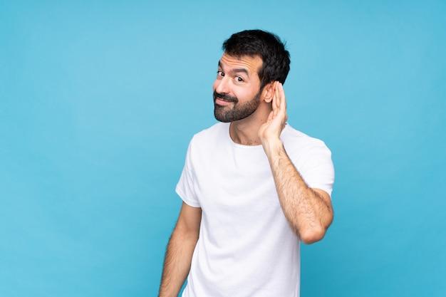 Jeune homme à la barbe sur mur bleu isolé, écouter quelque chose en mettant la main sur l'oreille