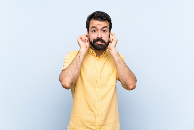 Jeune homme à la barbe sur un mur bleu isolé frustré et couvrant les oreilles