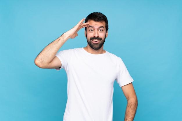 Jeune homme à la barbe sur un mur bleu isolé vient de réaliser quelque chose et a l'intention de la solution