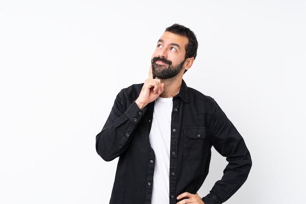 Jeune homme à la barbe pense à une idée en levant