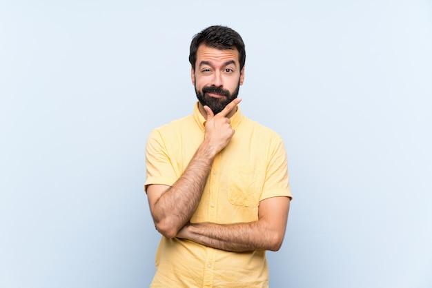 Jeune homme à la barbe sur la pensée de mur bleu isolé