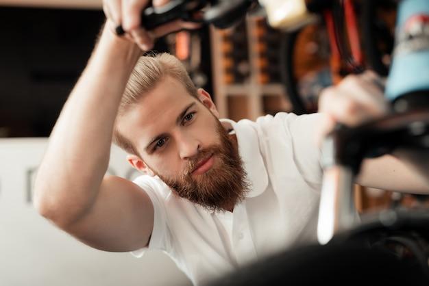 Un jeune homme avec une barbe regarde les détails de la bicyclette