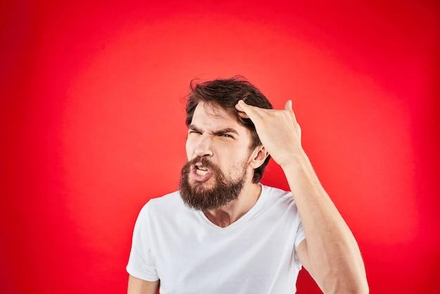 Un jeune homme avec une barbe en t-shirt montre différentes émotions, amusement, tristesse, colère sur l'espace