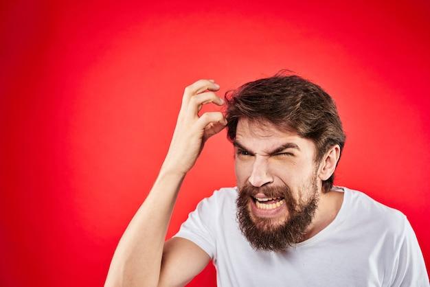 Un jeune homme avec une barbe en t-shirt montre différentes émotions, amusement, tristesse, colère