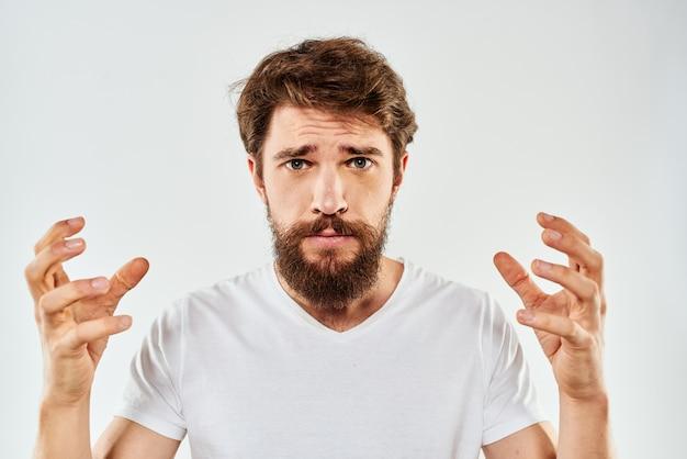 Un jeune homme avec une barbe en t-shirt montre différentes émotions, amusement, tristesse