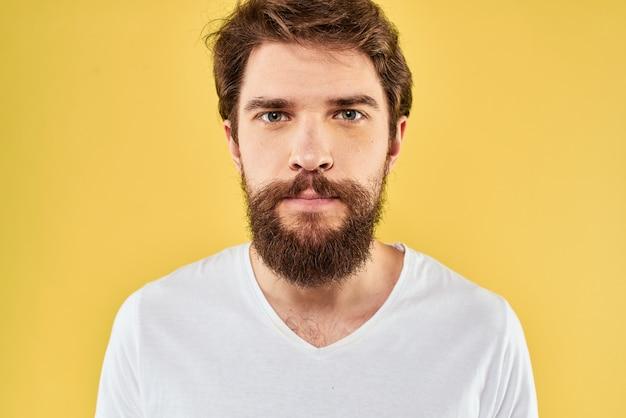 Un jeune homme avec une barbe en t-shirt montre différentes émotions