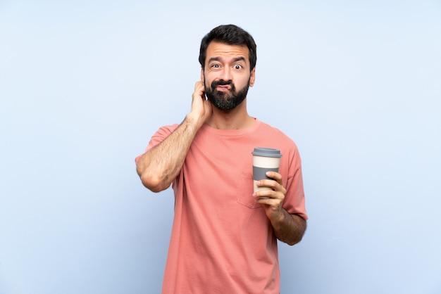 Jeune homme à la barbe tenant un café à emporter sur bleu ayant des doutes