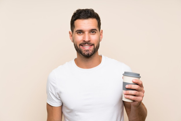 Jeune homme à la barbe tenant un café à emporter sur bleu isolé souriant beaucoup