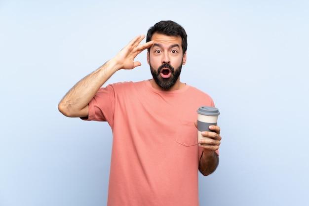 Jeune homme à la barbe tenant un café à emporter sur fond bleu vient de réaliser quelque chose et a l'intention de la solution