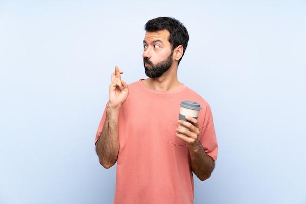Jeune homme à la barbe tenant un café à emporter sur un mur bleu isolé avec les doigts qui se croisent et souhaitant le meilleur