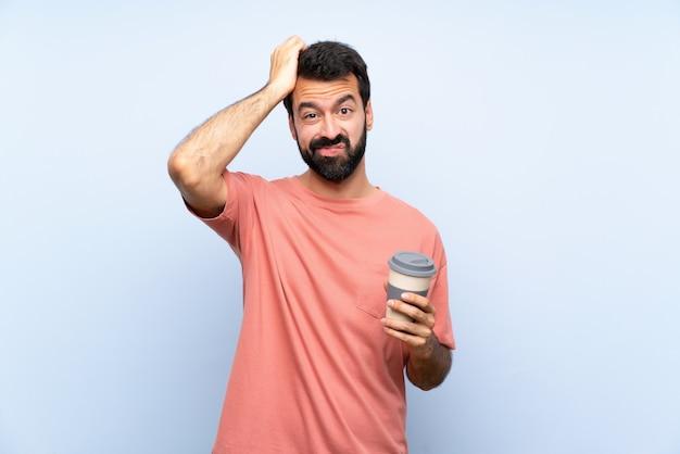 Jeune homme à la barbe tenant un café à emporter sur un mur bleu isolé avec une expression de frustration et ne comprenant pas