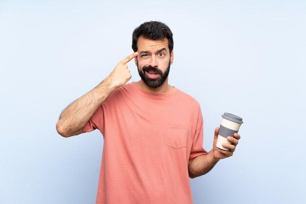 Jeune homme à la barbe tenant un café à emporter sur un mur bleu isolé, faisant le geste de la folie mettant le doigt sur la tête