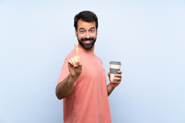 Jeune homme à la barbe tenant un café à emporter sur un mur bleu isolé montrant et en levant un doigt