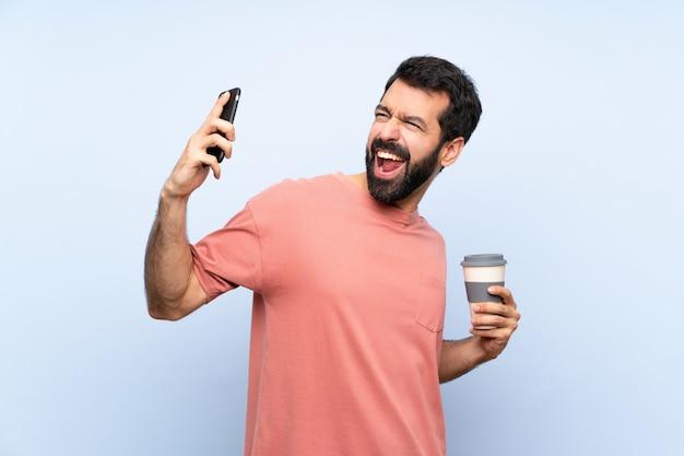 Jeune homme à la barbe tenant un café à emporter sur un mur bleu isolé avec téléphone en position de victoire