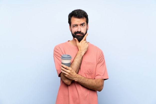 Jeune homme à la barbe tenant un café à emporter sur la pensée de mur bleu isolé