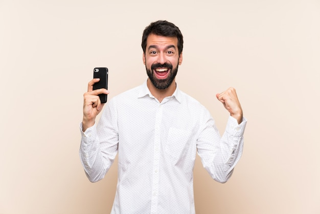 Jeune homme à la barbe tenant un mobile surpris et envoyant un message