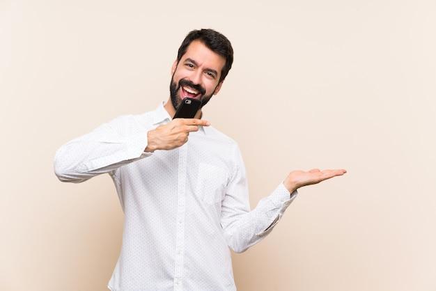 Jeune homme à la barbe tenant un mobile tenant une surface imaginaire sur la paume pour insérer une annonce