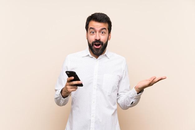 Jeune homme à la barbe tenant un téléphone portable avec une expression faciale choquée