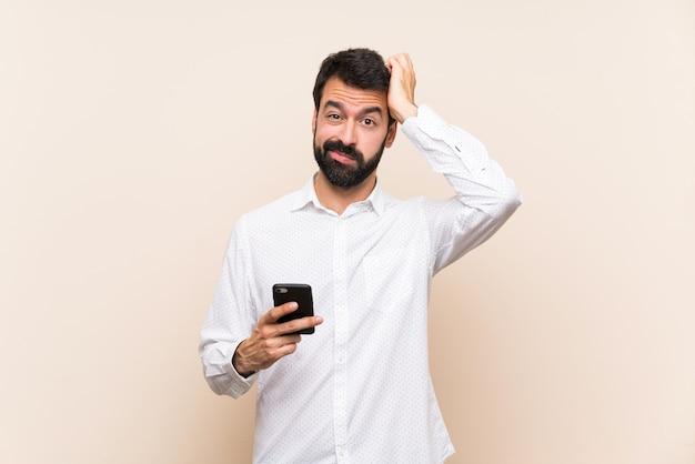 Jeune homme à la barbe tenant un téléphone portable avec une expression de frustration et de non compréhension