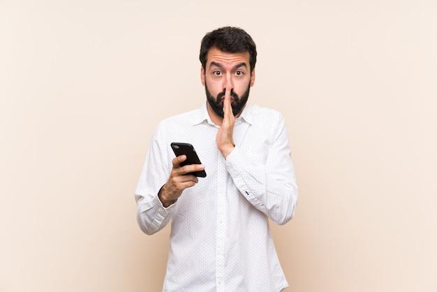 Jeune homme à la barbe tenant un téléphone portable garde la paume de la main. personne demande quelque chose