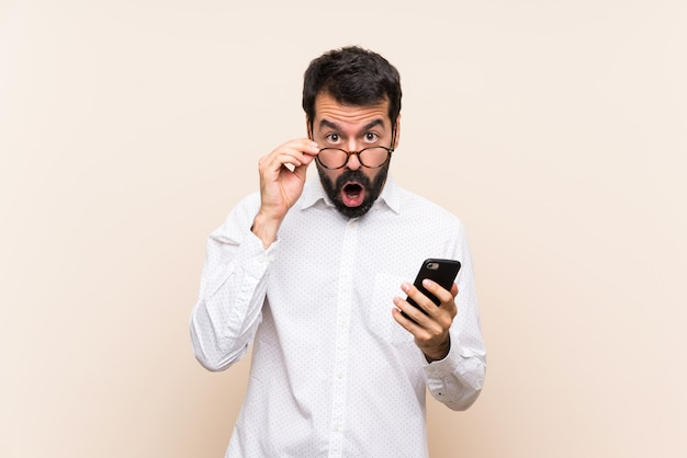 Jeune homme à la barbe tenant un téléphone portable avec des lunettes et surpris