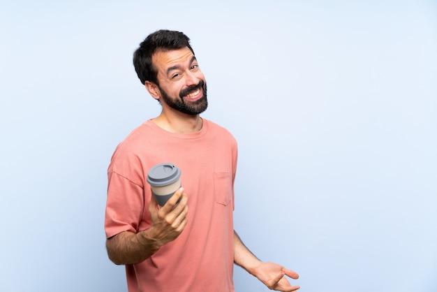 Jeune homme, à, barbe, tenue, a emporter, café, sur, isolé, mur bleu, sourire