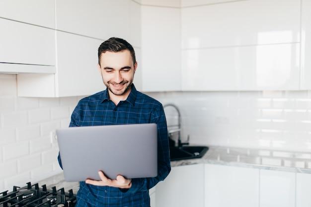 Jeune homme à la barbe travaillant sur un ordinateur portable dans la cuisine un mec heureux est assis dans la cuisine et bavarde avec ses amis