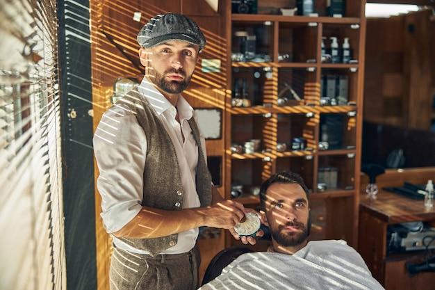 Un jeune homme et un barbier élégant tenant un blaireau regardant la caméra