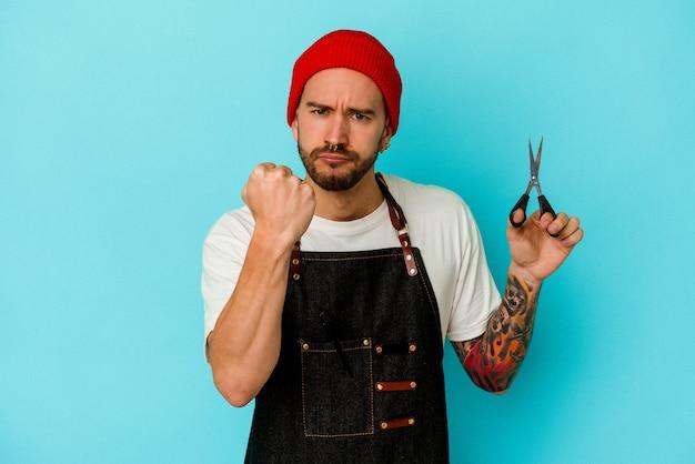 Jeune homme barbier tatoué isolé sur fond bleu montrant le poing à la caméra, expression faciale agressive.
