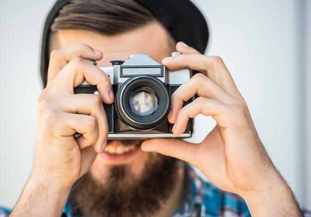 Jeune homme barbu avec appareil photo vintage fait une photo.
