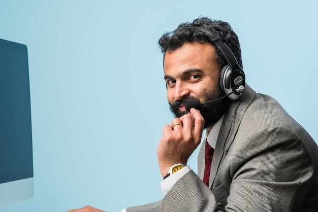 Jeune homme barbu asiatique indien en costume dans un centre d'appels, à l'intérieur, écoutant des écouteurs, naviguant sur un ordinateur ou ayant un appel vocal